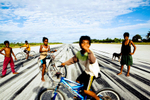 Children play on the airport landing strip. Tarawa Island, Kiribati.