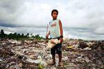 Boy picks through waste dump beside the Port for useful items. This dump was created in 2002 as a response to the governemnt recognised {quote}Waste Crisis{quote} in the 1990's. South tarawa, Kiribati.