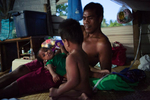 A Father relaxes with his two sons in their home in Ttebikenirkoora Village, Tarawa, an area that has been particularly affected by the rising sea level. THey must now swim home at high tide.