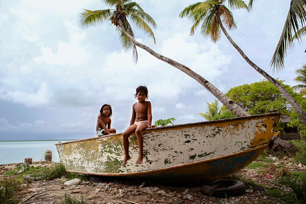 Two little girls play on a boat, lagoon side. Tarawa, Kiribati.