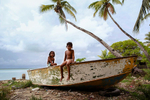 Two little girls play on a boat, lagoon side. Tarawa, Kiribati.