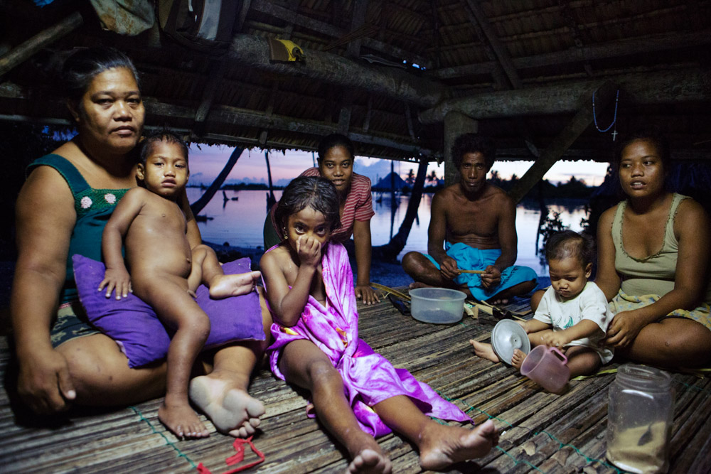 Tebunginako Village, Abaiand Island. A family relax in their common living area. The high tide now separates them from the rest of the village. They say this is a reletively new phenomenon that has gotten progressively worse over the last 15 years.