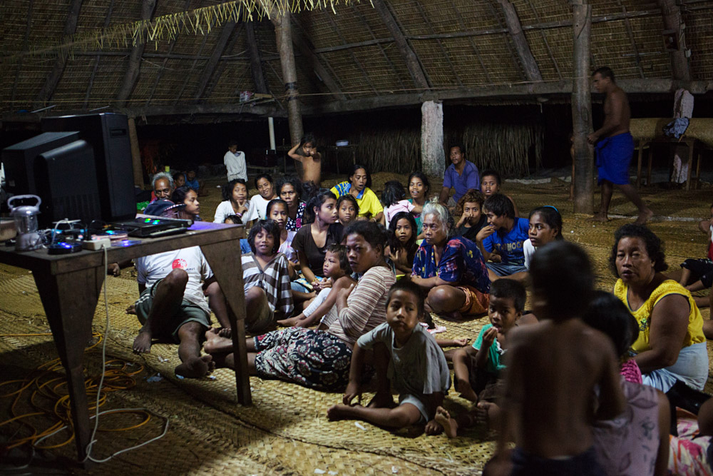 The community gathers for a movie night at the Maneaba (meeting house), Taburao Village, Abaiang Island, Kiribati.