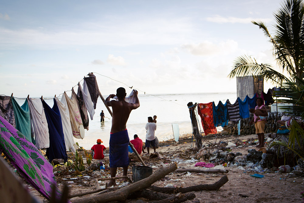 A man hangs out his laundry, Bairiki Village, Tarawa Island, Kiribati. This is one of the most high density slum areas in Kiribati.