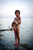 Girl with pig swimming on the foreshore of her village. Bairiki Slum, Tarawa Island, Kiribati.