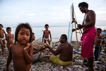Chilren watch while the men make toy sailing boats. Bairiki Village Slum,Tarawa Island, Kiribati.