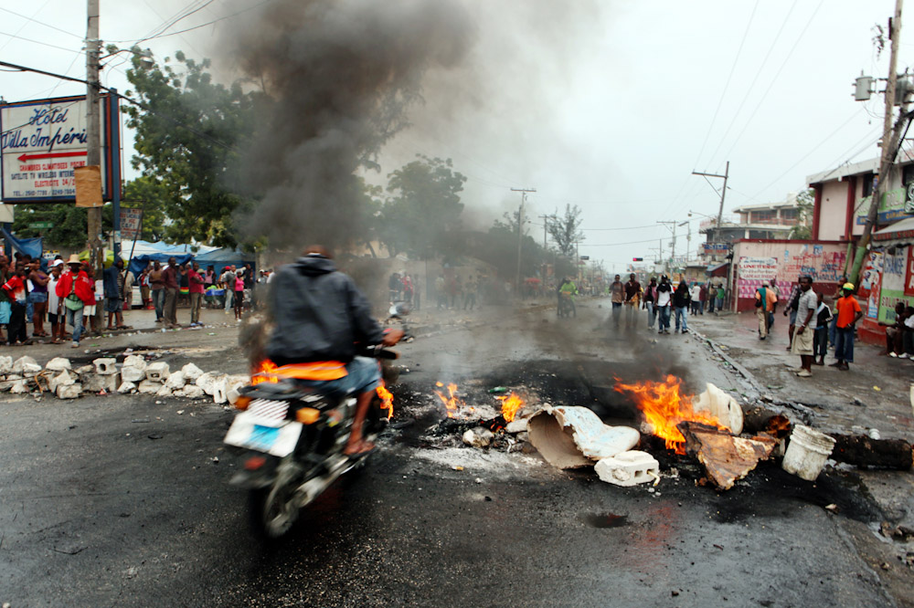 Motorbikes ride through blockades at Delmas and 33, near Petitionville, Port Au Prince. Barriors have been set up as part of a political manifestation.
