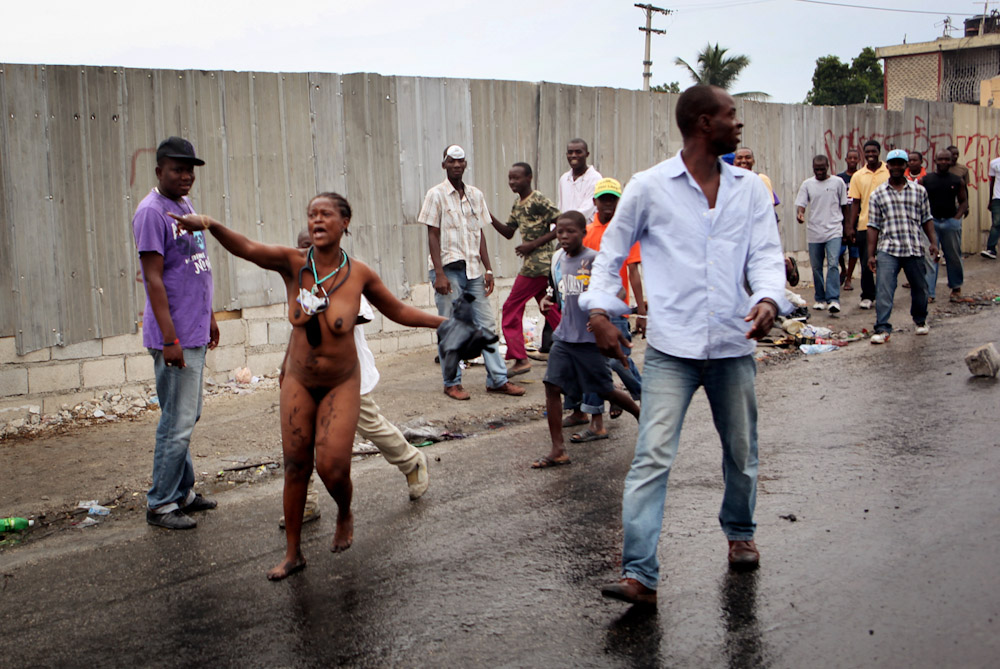 Upset woman runs through the street naked during Political manifestation near Petitionville, Port Au Prince