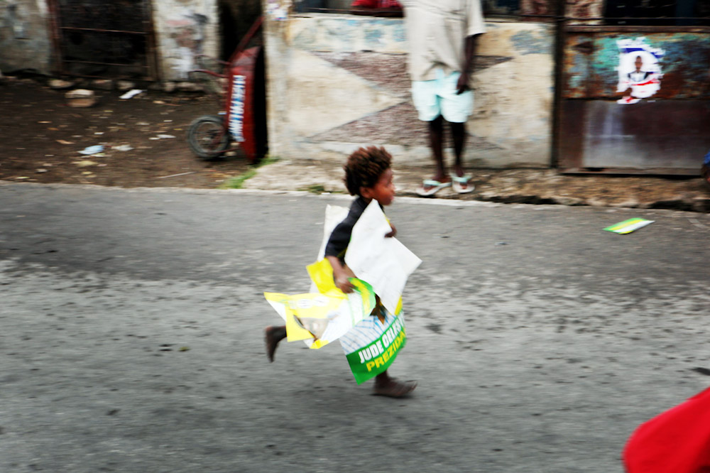 Small child runs away with Celestin Posters during political manifestation in the streets of Cite Soleil. Haiti's most impoverished slum.