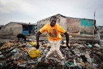 A boy spontaneously poses strangely for the camera on a pile of garbage in Cite Soleil, inviting me to photograph a parody of the way westerners like to portray Haitians in popular media.