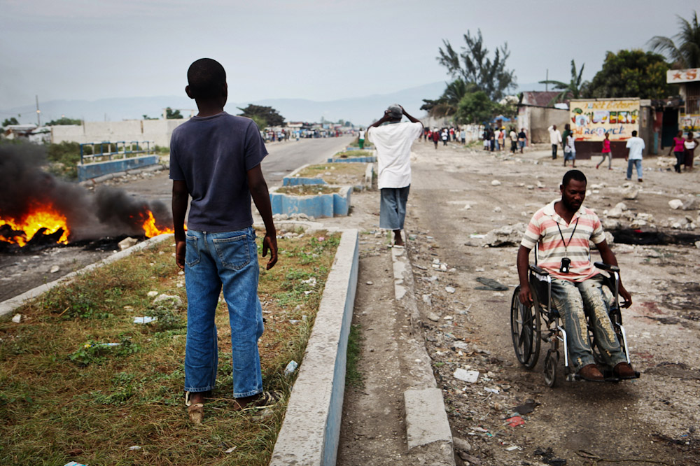 Fires burn and gunshots are fired by neighbouring tent cities supporting opposing parties on the outskirts of Cite Soleil during a political manifestation.