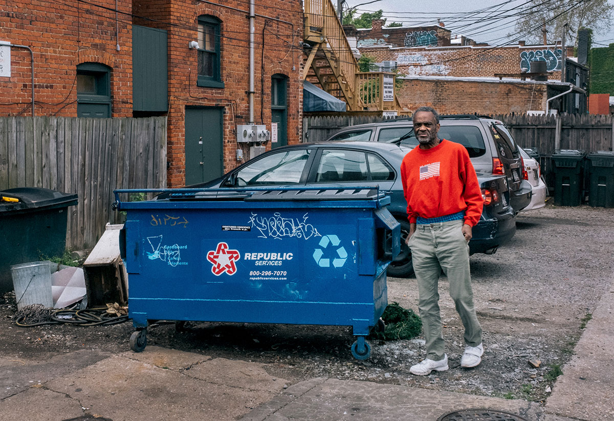 A man checks out several trash cans in the neighborhood to look for what he needs.