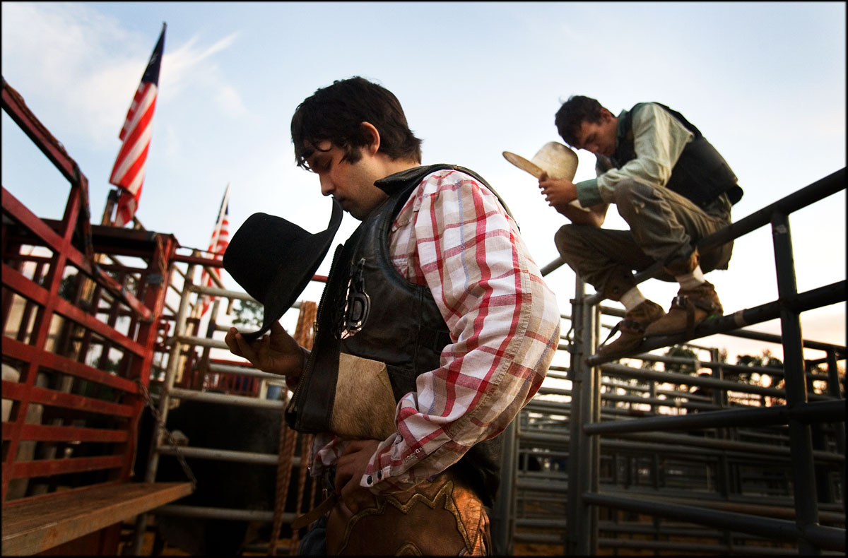 Shea Willard, of King, NC, center, and Brandon Chambers, of Newport, NC, bow for 'Cowboy's Prayer' before their bull riding competition.