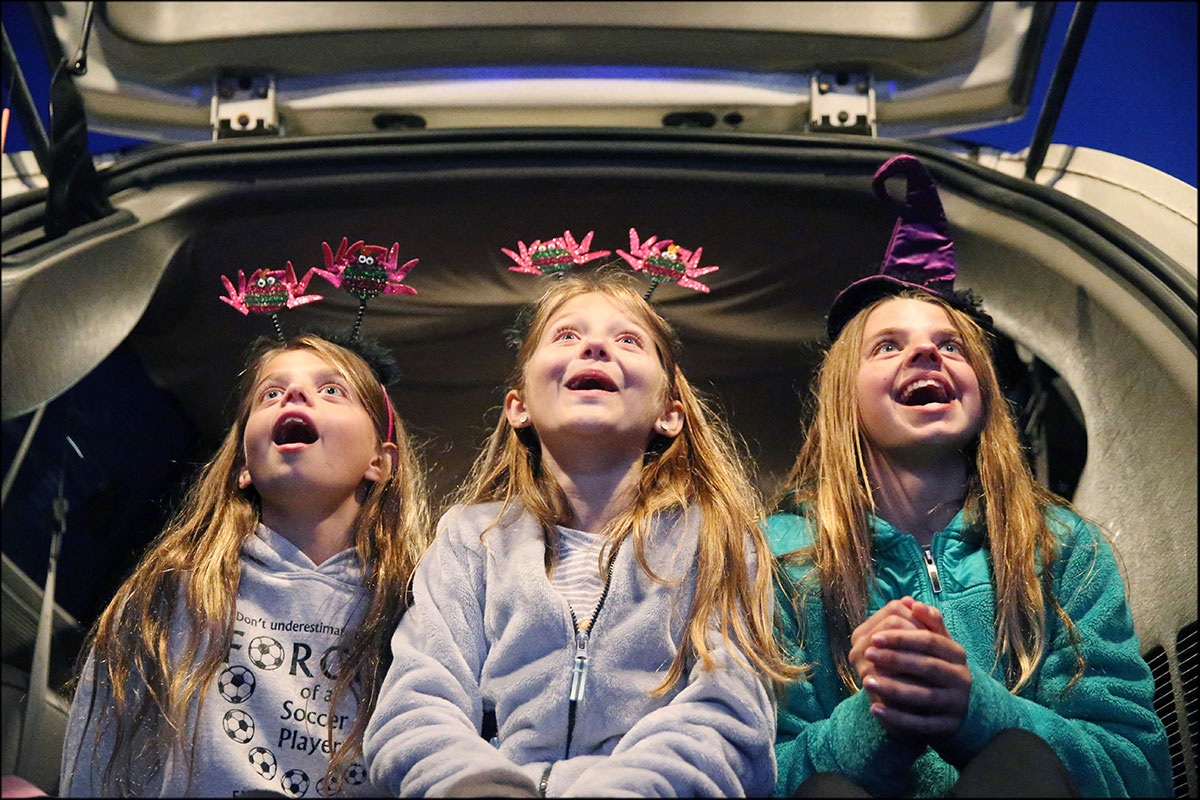 From left, Axandrea Chittenden, 10, Artela Aljiji, 10, and Mary Ann Chittenden, 14, of Fluvanna, were excited to see Charlie Brown and Snoopy in Peanuts short movie on a screen as they waited main movies on a car at Goochland Drive-In Theater in Hadensville.