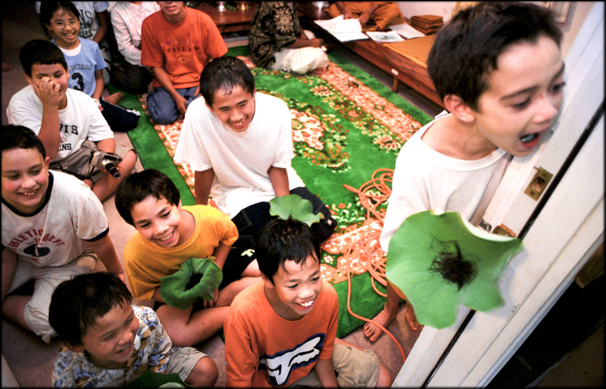 Candidates for novice monks laugh during a hair cutting ceremony at Pasantidhamma Buddhist Temple. As part of tradition, Jacob Read, right, and other candidates are holding their first-cut locks of hair on lotus leaves.