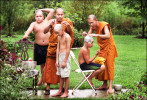 Senior monks Methawee Bhikku and Phramaha Putthachak Buddhisaro shave heads and eyebrows of novice monks. Shaving is symbolic of purifying one's self and peeling away the temporary from one's body.