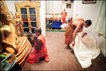 James Rimnongrua, left, bows to Buddha as Methawee Bhikku, a senior monk, helps Joseph Bray get comfortable at the end of the day. Before sleep, the young monks bow three times to Buddha and their teachers to show respect and gratitude.