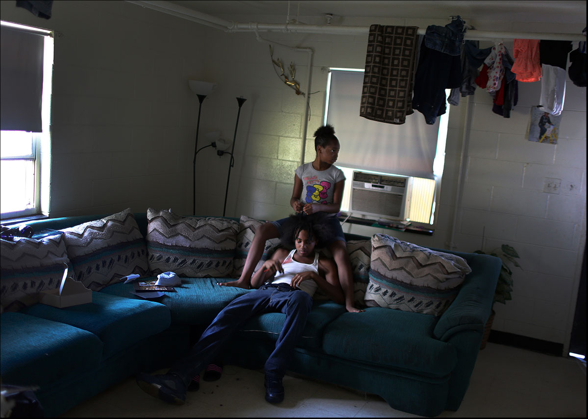 Toniyah {quote}Butta{quote} Ross, 12, braids the hair of her brother Dalen Smith at their home in Mosby Court, one of housing projects in Richmond. {quote}It's violent and I don't like to go anywhere,{quote} Toniyah said of her neighborhood, {quote}Because it's a lot of shootings and I don't want to get hurt.{quote}
