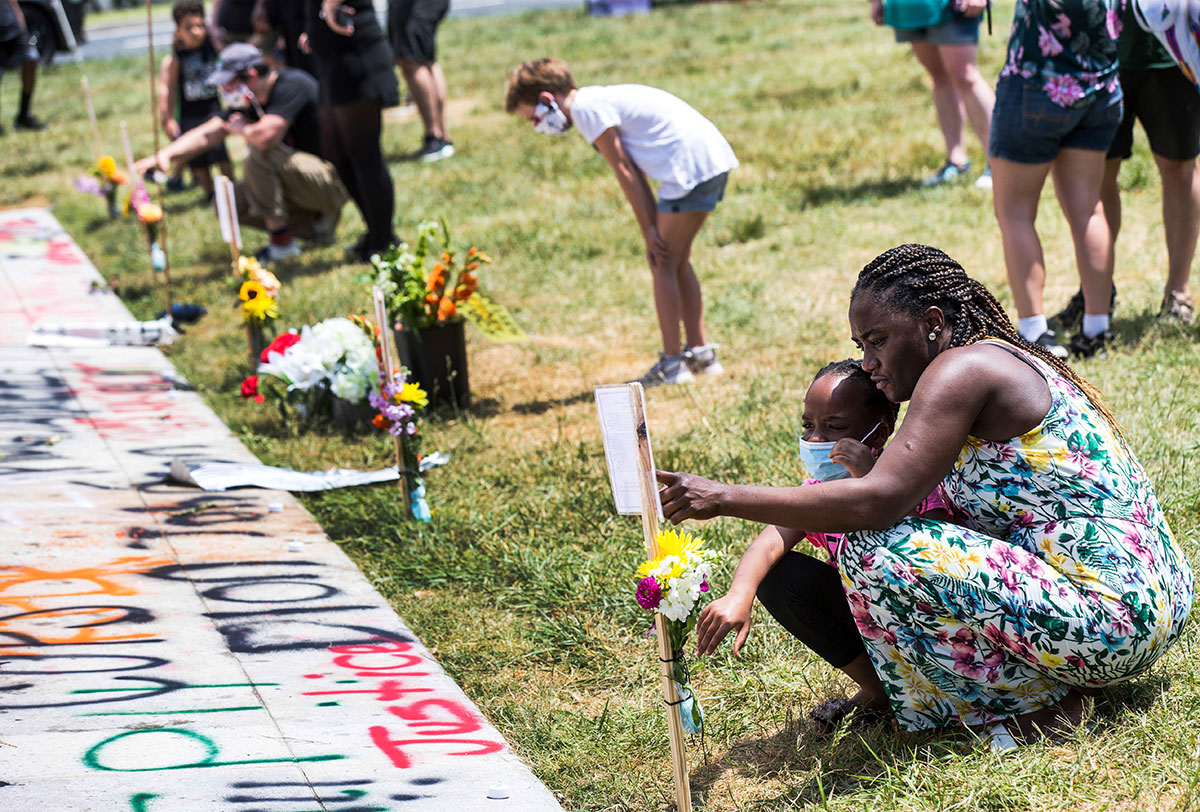 Visitors check out a memorial of Freddie Gray and other memorials at Robert E. Lee statue.