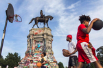 From center to right, Amar Bullock, 13, Zykuan Williams, 13, and Anthony Rosser, 12, play basketball near the sigh of Marcus-David Peters Circle at Robert E. Lee monument.