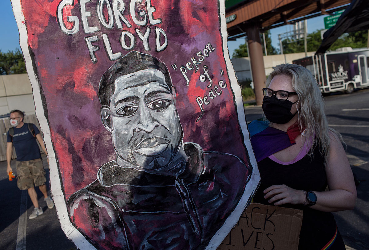 Kathryn Heckroth of Charlottesville holds a banner with the portrait of George Floyd as Heckroth attends Stonewall Rising: LGBTQ March for Black Lives Matter.