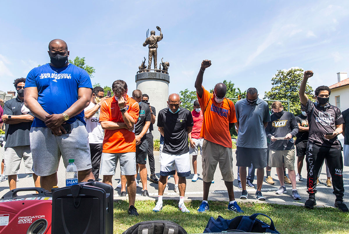 Coaches from all of Virginia, take moment of silence as they gather to support their athletes at Arthur Ashe statue.