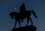 The crescent moon sets on top of Robert E. Lee Monument.