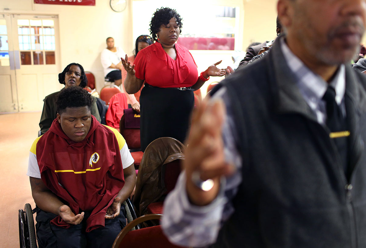 Edward prays with his mother, Lawanda Booker, standing next to Edward, during a church service at Crusade for Christ Christian Church Ministries in Richmond. Edward often recites the note from his sister, Shakiria Miller, 'God gives his hardest battles to his strongest warriors.' {quote}That's what got me through physical therapy, those hard days and me passing out and stuff like that. That's what got me through that hard time,{quote} Edward said of the note.