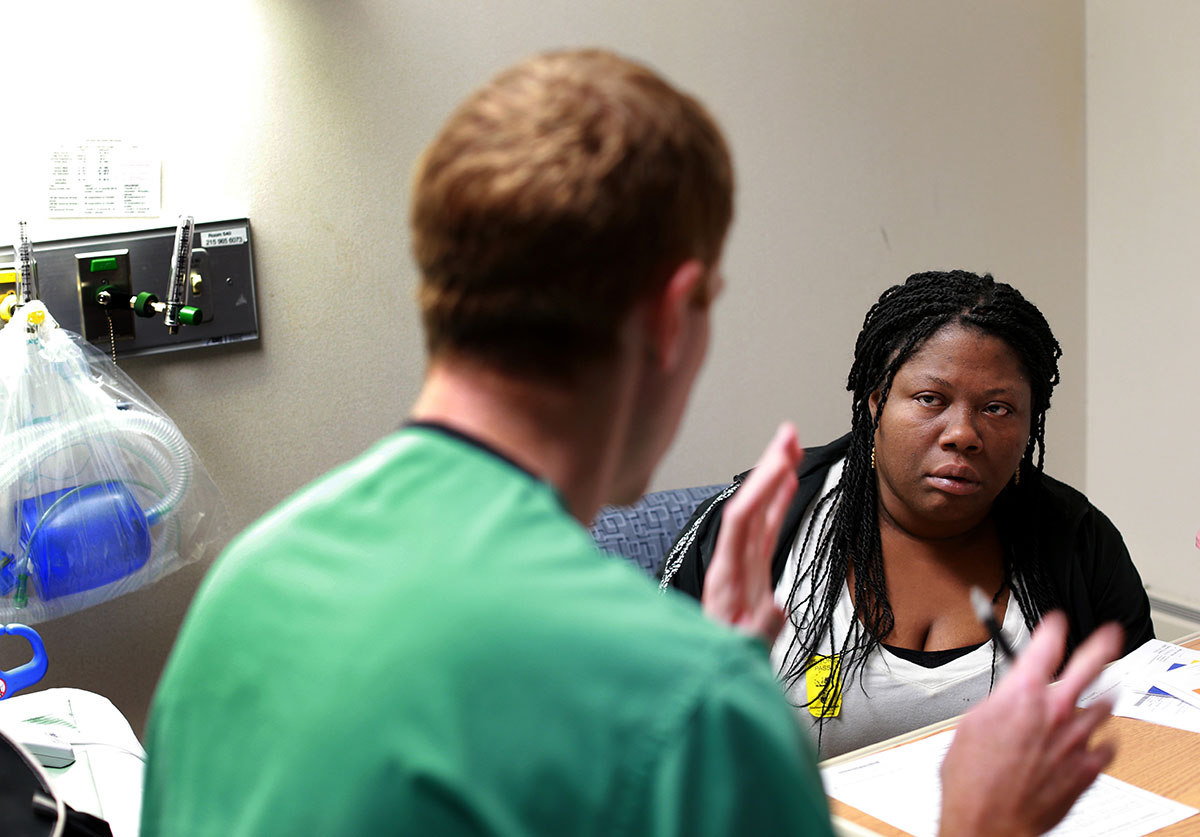 Lawanda Booker listens carefully to Joshua Pahys, an orthopaedic surgeon, about Edward's spinal fusion surgery at Shriners Hospitals for Children in Philadelphia.