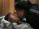 Lawanda Booker kisses her son, Edward, as she sees Edward for the first time after 13-hour spinal fusion surgery at the intensive care unit of Shriners Hospitals for Children in Philadelphia. {quote}My mom, she is very strong. She does everything on her own. She is very strong woman'{quote}Edward said later.