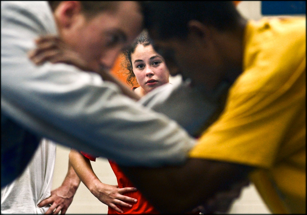 Warry Woodard eyes on her teammates, Jeremy Riddick, left, and Roy Gilbert, Jr., as they learn techniques during their daily practice. {quote}All my goals, when I started out, were not to cry about losing, not to get pinned{quote}, Warry says. After six years of wrestling and as a high school junior now, her aim is being accepted to Cumberland College in Kentucky, which has one of the best women's wrestling program in the nation.