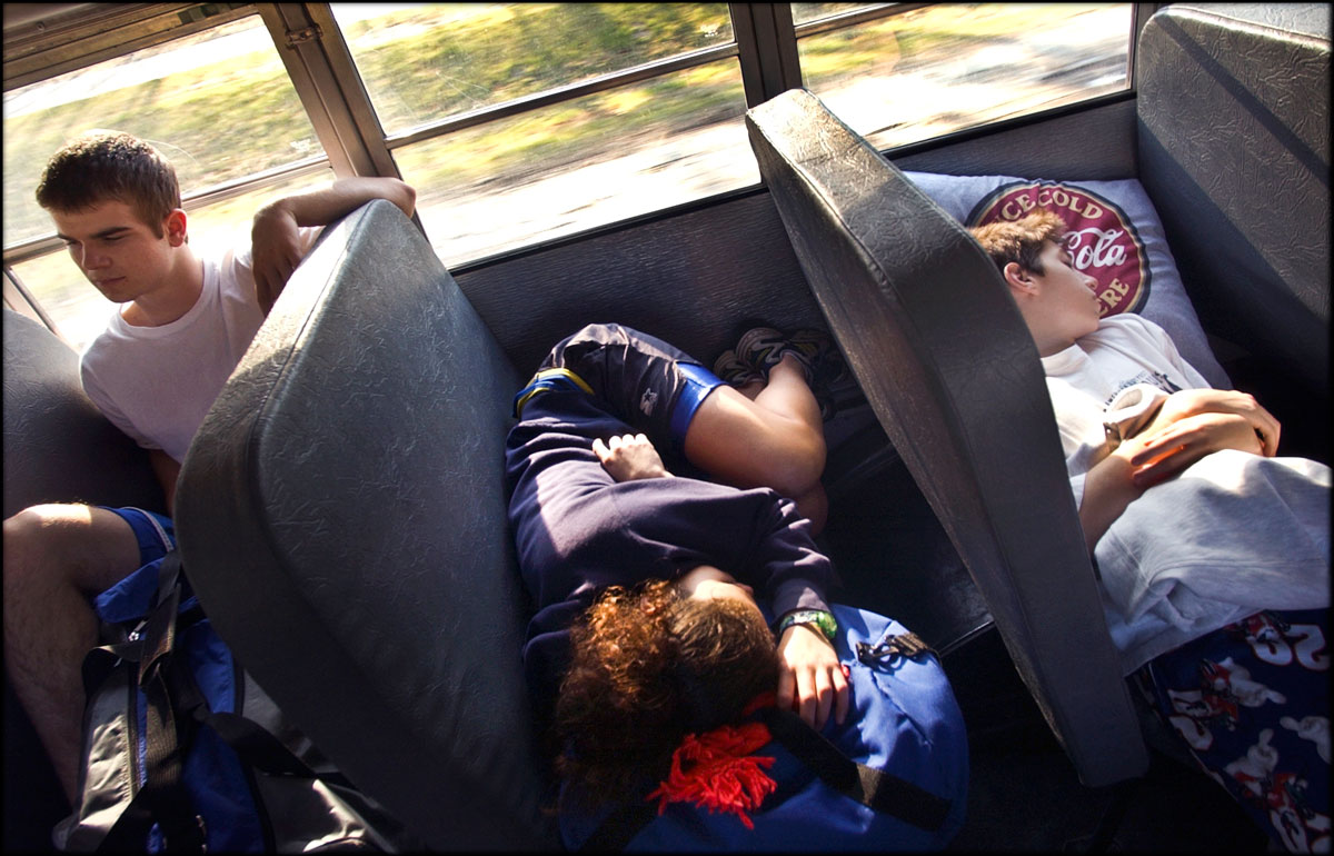 On the way to their matches, Warry and her teammates, Collin Jeffers, left, and Justin Wallace rest and relax in the school bus.