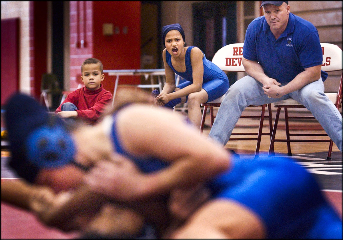 Haille Cloutier, 10, cheers Warry, foregournd, with her brother, Roger, Jr., 8, left, and coach Roger, Sr., as Warry has an exhibition match against Karryssa Toliver during United States Girls' Wrestling Association's Virginia State Championships. {quote}She is my role model,{quote} Haille says of Warry, {quote}I want to be like her.{quote} Haille and Warry attend many girls' tournaments together.