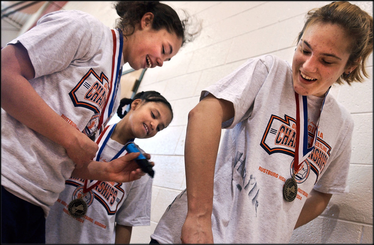 After winning their Virginia Girls Wrestling championships in Rustburg, Warry Woodard, Haille Cloutier, center, and Candice Hornbeck, right, autograph their names on each other's T-shirts.