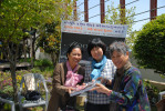 Left: Kang Mi-kyoung, director of Hanbit Shelter for Women, receives copy of {quote}Moon Tides--Jeju Island Grannies of the Sea.{quote} Middle: Han Young-sook, translator and interpreter. Right: Author