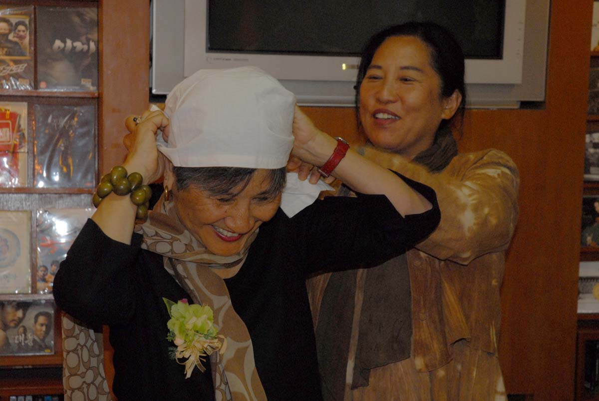 Kang Mi-kyoung, director of Hanbit Shelter for Women, helps author don traditional haenyeo clothing given to her by one of the haenyeo divers.