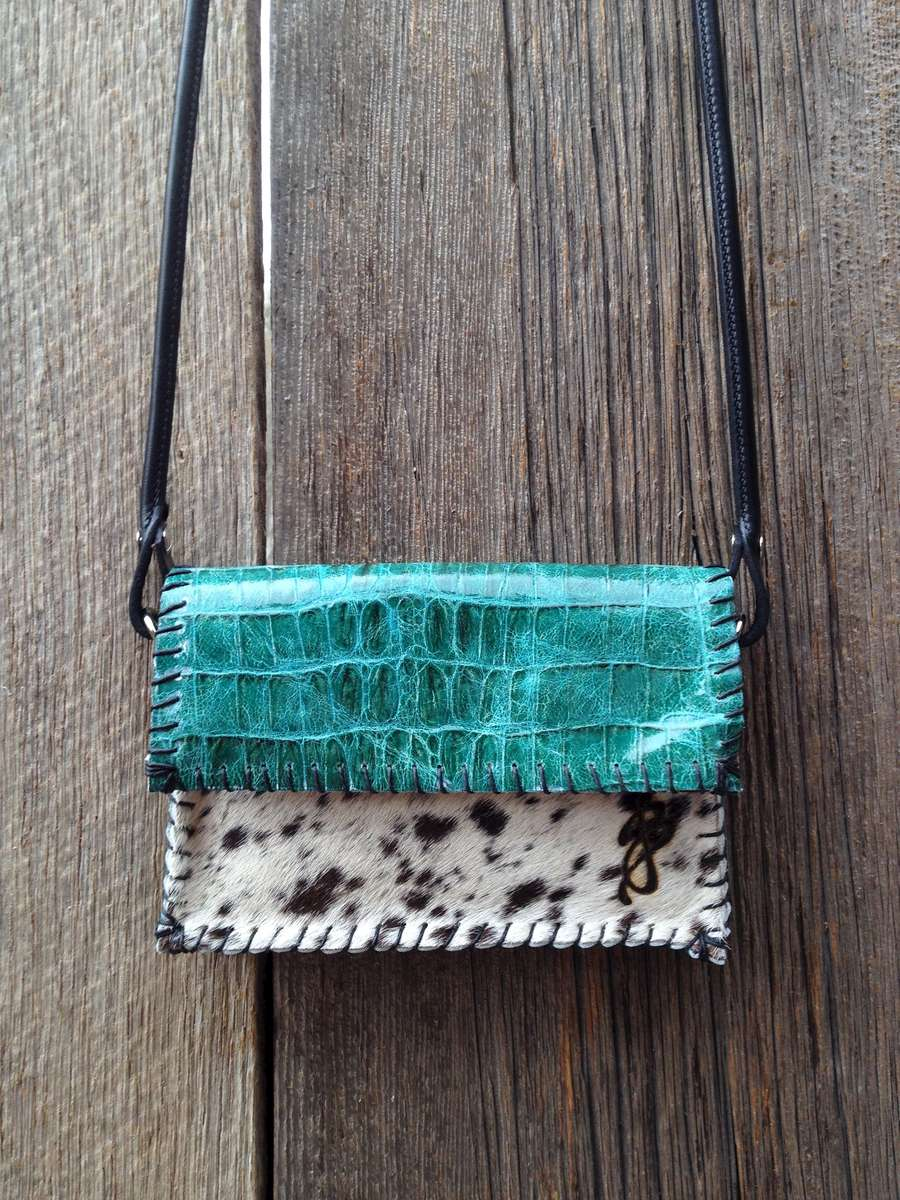 Teal Green Snake Embossed Leather paired with a Black & White Brazilian Hair-On Cowhide front.   Black Amish Horse Bridle Strap