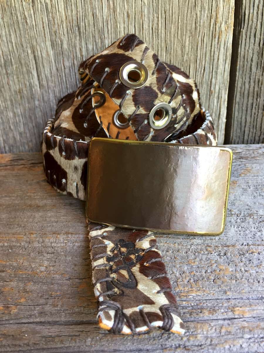 An animal print hair-on hide belt, backed with a tone-on-tone orange floral print lining.  Paired with an artisan hand forged buckle.