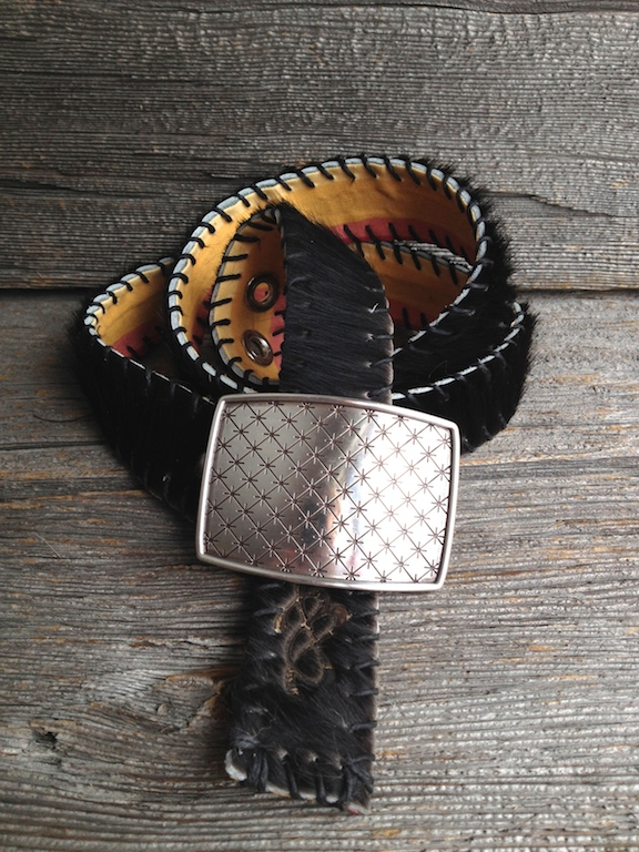 Black Hair-on Brazilian Cowhide, paired wth a brightly striped cotton lining.   Assorted buckle