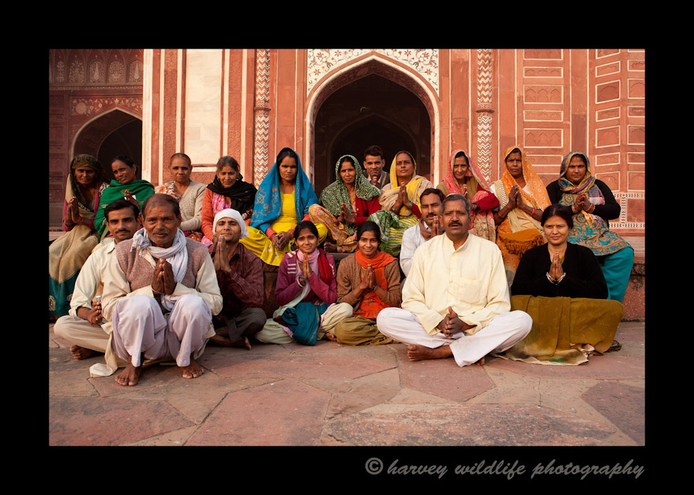 "This Indian family (and friends) pose for a few photographs in front of the mosque east of the Taj Mahal. They demonstrate their peaceful ""Namastae"" pose for us as we photograph them."