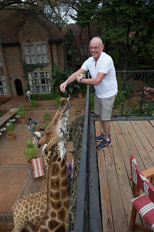 Pat Feeding a Giraffe from a room at Giraffe Manor