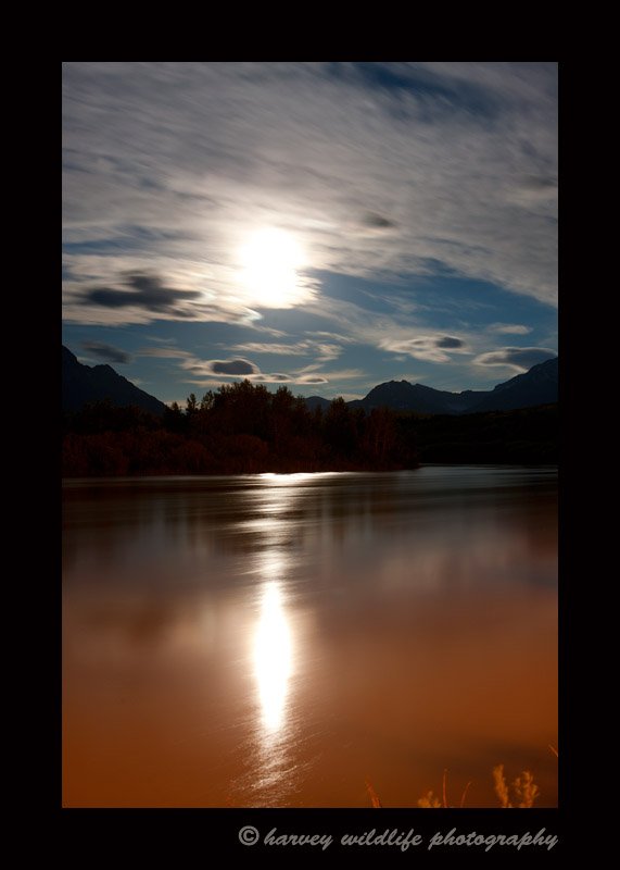Behind the clouds is a full moon reflecting over Waterton Lakes, Alberta, Canada.