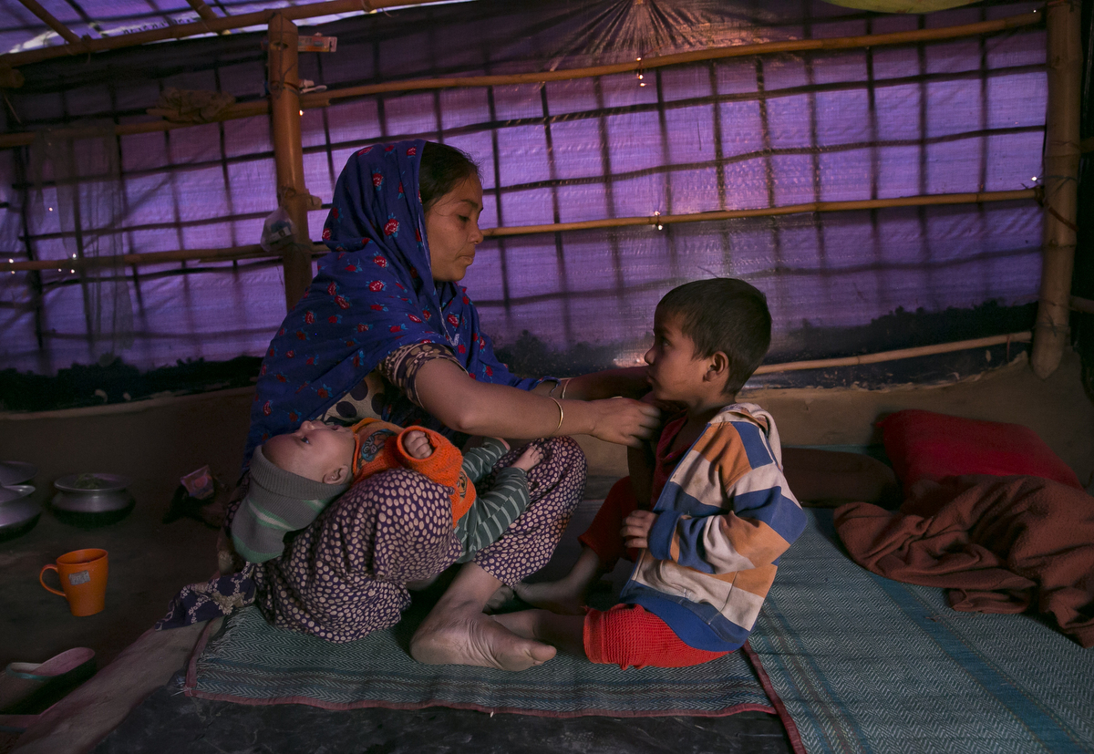 Asma is seen with her children. Asma came from Buthidaung township in Burma. The military torched the houses in her village and killed her husband. She walked for 7 days to Bangladesh, carrying her two children, while she was 6 months pregnant. She gave birth in a shack in the jungle 5 days after she arrived in Bangladesh.