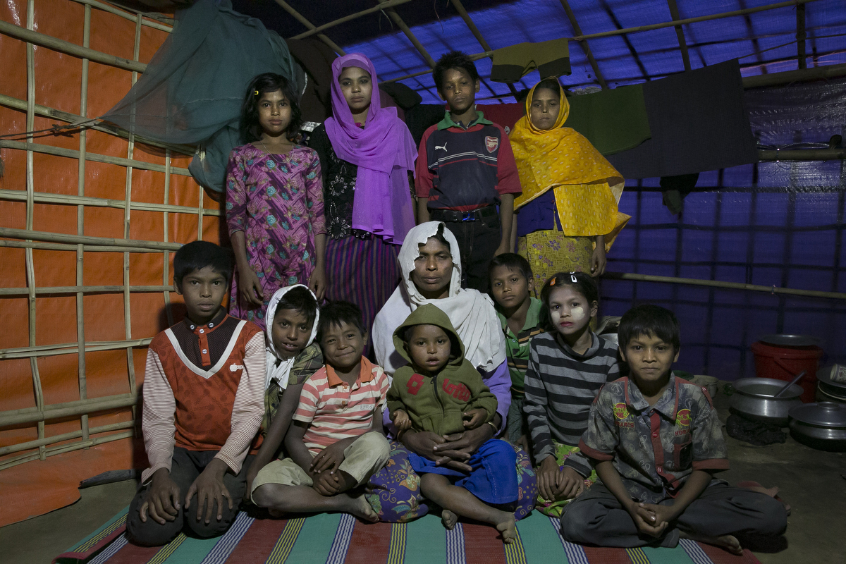 Samuda (center, white)  poses for a photo. Samuda has taken in 5 of her sisters kids, and she has 6 of her own kids, from Buthidaung township. The military came and took away her husband. She ran and hid in the jungle and watched as the military torched the houses in her village. While she fled to Bangladesh she found her sisters kids. They told her their mother and father had been shot as they ran away from the military. She likes living in the camp because the other women help her look after the kids. {quote}During the daytime we are traumatized and sad. The only time we are in peace is when we go to sleep. The kids cry and ask what will happen to them? When they cry my own kids start to cry. I feel lost and I don't know what to do.{quote}