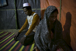 Amina Begum, 15 , sits with her new husband, 22 year old Munir, after their marriage ceremony in a Bangladesh refugee camp in Cox's Bazar, Bangladesh. Her husband, Munir, 22, is from same village. Amina and her family fled their village after the August 25th attack when the army and Buddhists opened fire on the village. They had to walk for 13 days to the Bangladesh border, sleeping in the forest and taking shelter in other villages on the way. Amina's father has 8 children, 5 girls and 3 boys. He says 'I already have a lot of daughters, if I marry them off it's good for me. If I get the opportunity I will marry the rest off as soon as possible. If I die, who will take responsibility for them?' Munir says 'I think 18 is the best age for a girl to get married, but we knew each other in the village so it's okay.'