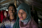 Rahul Amin, 20, and Sabakur Nahar, 15, pose for a photo in Cox's Bazar, Bangladesh. They were married two months ago in a Bangladesh refugee camp. Rahul is from Tula Toli and Sabakur is from Bouli Bazar. They both fled to Bangladesh after the August 25th attack. Rahul lost 20 relatives in the attack and spent days walking to Bangladesh, hiding in the forest and drinking water from the paddy fields along the way. Sabakur saw her father killed by the military and lost 6 relatives during the attack. She got separated from the rest of her family and spent 8 days walking to Bangladesh. Sabakur and Rahul met in Bangladesh at the Kutupalong transit center. He says that he thought she was beautiful so he approached her and they started talking. After 3 days he proposed marriage to her. She told him yes, but that she couldn't marry him until she found her family. Eventually she gave up hope and they were married a few days later. A few weeks after that she located her family in a camp. Rahul says 'Her age didn't matter to me, her body structure isn't young and small, she looks older, so it's okay. In our culture, women who look older have to get married. If other people see her they'll criticize her family, saying your daughter is getting older she needs to get married now. In Islam, any girl who looks older and is seen outside of the house, it's bad for her family. In the Koran, it says that if anyone sees a girl outside of the house, she will be cursed.' Sabakur says 'I wanted to wait until I was 18 to get married, 15 is too young. I agreed because I didn't have my family here. If I was in Myanmar I never would have agreed to get married. I was all alone here, so I agreed.'