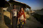 Abdul Karim, 20 and Arifa Begum, 16, pose for a photo in Cox's Bazar, Bangladesh. They were married in a Bangladesh refugee camp one week ago. Arifa fled to Bangladesh from Bouli Bazar in Myanmar and Abdul fled from Tula Toli, both after the August 25th attack. Abdul says 'I didn't want to get married, I wanted to wait until I can go home to Myanmar. I have no work here, how can I support a family? My father wanted me to get married because food ration cards are given to individual families here'. Arifa says, 'I didn't want to get married, but I can't deny my parents wishes. My father wanted me to get married, I don't have a choice. I have to do what he says'. Arifa's father, Abdul Mabub says 'I don't have enough food to feed her. The camp is unsafe and marriage means safety. I'm not home to look after her all the time, now her new family looks after her and she's not my responsibility anymore'.