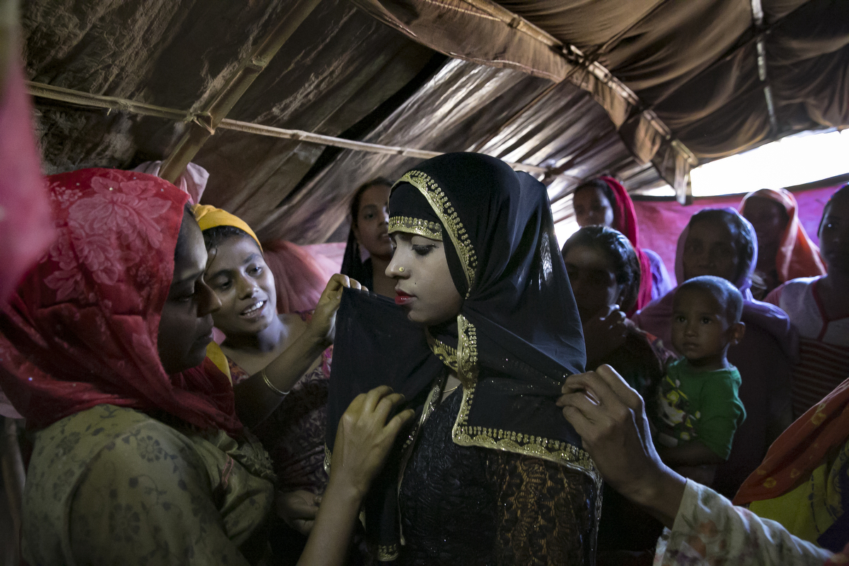 Nur Begum, who doesn't know her age but thinks she is between 14 and 16 years old, is seen on the day of her wedding to Rayeed Alam, 20, in a Bangladesh refugee camp in Cox's Bazar, Bangladesh. Rayeed came to Bangladesh with his family shortly after the August 25th attack. He says the military attacked his village and shot people, burned houses and raped women. It took him 3 days to walk to the Bangladesh border. Rayeed's parents arranged the marriage because all of his sisters are already married and his mother needed someone to cook and look after her and her husband. Nur Begum said that her parents arranged the marriage for her and she had no choice in the matter.