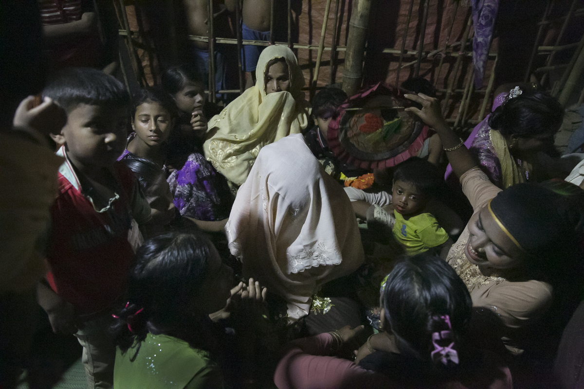 Women crowd around Nur Begum, who doesn't know her age but thinks she is between 14 and 16 years old, on the day of her wedding to Rayeed Alam, 20, in a Bangladesh refugee camp in Cox's Bazar, Bangladesh. Rayeed came to Bangladesh with his family shortly after the August 25th attack. He says the military attacked his village and shot people, burned houses and raped women. It took him 3 days to walk to the Bangladesh border. Rayeed's parents arranged the marriage because all of his sisters are already married and his mother needed someone to cook and look after her and her husband. Nur Begum said that her parents arranged the marriage for her and she had no choice in the matter.