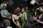 Women dance around Nur Begum (not pictured) who doesn't know her age but thinks she is between 14 and 16 years old, on the day of her wedding to Rayeed Alam, 20, in a Bangladesh refugee camp